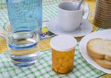 Läkarbehandling under frukosten, kapslar bredvid ett exponeringsglas av vatten, begreppsmässig bild arkivbild
