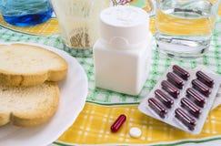 Läkarbehandling under frukosten, kapslar bredvid ett exponeringsglas av vatten, begreppsmässig bild royaltyfri bild