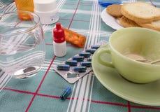 Läkarbehandling under frukosten, kapslar bredvid ett exponeringsglas av vatten, begreppsmässig bild arkivbilder