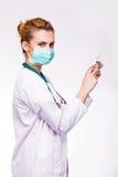 Läkare som förbereder en injektionsspruta och ser till kameran Arkivbild