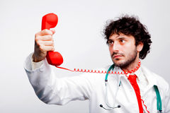Läkare som ser telefonen Arkivbild