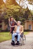 Läkarundersökning: anhörigvårdaredotter med den höga mannen i rullstol Royaltyfria Foton