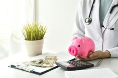 Läkarundersökning- och sjukförsäkringbegrepp, hållande spargris för doktor och pengar i sjukhusbakgrund arkivbild