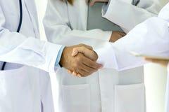 Läkarundersökning- och sjukvårdbegrepp Ung medicinsk folkhandshaking royaltyfri foto