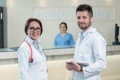 Läkarundersökningen bemannar att ha diskussion i modern sjukhuskorridor Arkivbild