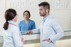 Läkarundersökningen bemannar att ha diskussion i modern sjukhuskorridor Arkivbilder
