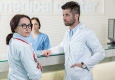 Läkarundersökningen bemannar att ha diskussion i modern sjukhuskorridor Arkivfoto
