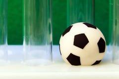 Läkarundersökningen skrapade provrör och en souvenirfotbollboll på en grön bakgrund Begreppspengar och sportar, medicin och fotbo Arkivfoto