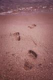 Lämna fotspår i sanden i havet Arkivbilder