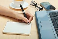 Lämnad-hander skriver i en anteckningsbok Arkivbild
