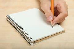 Lämnad-hander skriver i en anteckningsbok Royaltyfri Fotografi