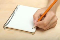 Lämnad-hander skriver i en anteckningsbok Arkivbilder