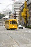 Lämnar den gula spårvagnen för klassikern av den Kumamoto staden med gul ginko lodisar Arkivfoton