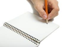 Lämnat-hander skriver i en anteckningsbok Royaltyfria Bilder