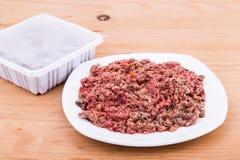 Lämplig emballerad finhackad hundmat för rått kött på plattan Arkivbilder