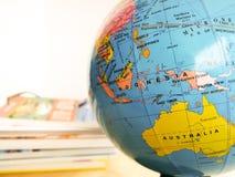 Länder und Kontinente schließen oben mit der Farbkarte auf einer Kugel mit Büchern im Hintergrund lizenzfreie stockfotos