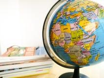 Länder und Kontinente schließen oben mit der Farbkarte auf einer Kugel mit Büchern im Hintergrund lizenzfreie stockfotografie
