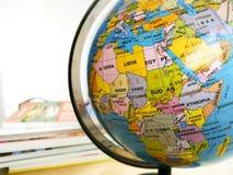 Länder und Kontinente schließen oben mit der Farbkarte auf einer Kugel mit Büchern im Hintergrund lizenzfreie stockbilder