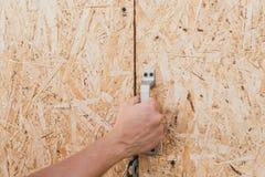Ländliche alte Tür des Sägemehls ein Mann öffnet eine Holztür stockbild