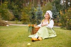 Ländliche Frau mit Korbsitzplätzen auf dem Rasen Stockbilder