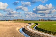 Ländliche gebogene Straße für Fahrräder im niederländischen Ackerland Stockfotografie