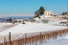 Ländliche Häuser und Weinberge auf schneebedeckten Hügeln stockbilder