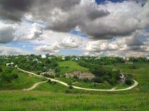 Ländliche Landschaft, Ansicht des Dorfs unter den grünen Hügeln, um die Landstraße überschreitet, Himmel mit enormen Gewitterwolk Lizenzfreie Stockbilder