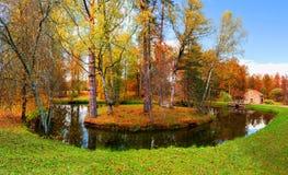 Ländliche Landschaft des Herbstes - Einsamkeitsinsel mit Teich und kleinem Haus auf dem Hintergrund Lizenzfreie Stockbilder