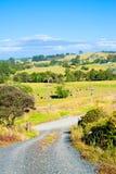 Ländliche Landschaft - eine wickelnde Schotterstraße unter Hügeln des Ackerlands an einem Tag des feinen Sommers lizenzfreies stockfoto
