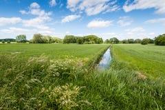 Ländliche Landschaft geschnitten durch einen reflektierenden Abzugsgraben Lizenzfreie Stockfotos