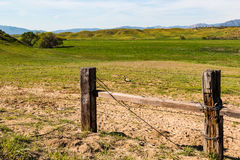 Ländliche Landschaft mit dem Zaun und dem Rollen von grünen Hügeln Lizenzfreie Stockbilder