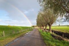Ländliche Landschaft mit einer Landstraße und einem Regenbogen Lizenzfreie Stockfotos