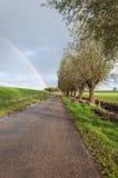 Ländliche Landschaft mit einer Landstraße und einem Regenbogen Stockfoto
