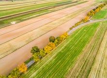 Ländliche Landschaft mit einer Straße, gesehen von der Vogel ` s Augenansicht Bebaute Felder im Herbst Straße durch die Felder Lizenzfreie Stockbilder