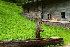 Ländliche Landschaft mit hölzernem Wasserbrunnen und einer alten alpinen Hütte nahe Falzthurnalm Achensee Seebereich, Österreich, Stockbild