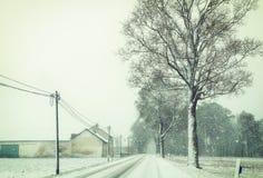 Ländliche Landschaft mit Straße und Bauernhof unter Schneefällen im Winter Lizenzfreie Stockfotografie