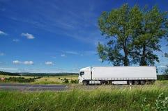 Ländliche Landschaft mit weißem LKW auf der Straße lizenzfreie stockfotografie