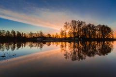 Ländliche Sommersonnenaufganglandschaft mit Fluss und drastischem buntem Himmel Lizenzfreies Stockfoto