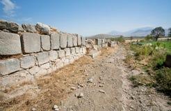 Ländliche Spur entlang der Steinwand eines mittelalterlichen Gebäudes zerstört in den Bergen Lizenzfreie Stockbilder