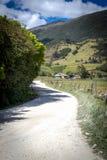 Ländliche staubige Straße mit Bergen im Hintergrund Lizenzfreie Stockfotos