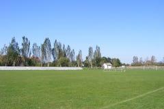 Ländlicher Fußball, Fußballneigung genommen von der Haupttribüne auf einem sonnigen Frühling, Sommertag Lizenzfreies Stockbild