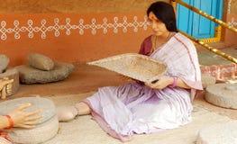 Ländlicher indischer Frauenfigürchengebrauch ein trennender Korb oder ein Fan, das Korn zu säubern Stockbilder