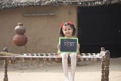 Ländlicher indischer Holdingschiefer des kleinen Mädchens zu Hause stockfoto
