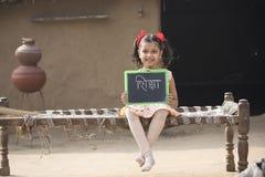 Ländlicher indischer Holdingschiefer des kleinen Mädchens zu Hause lizenzfreies stockbild