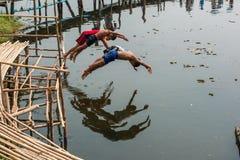 Ländlicher Kinderlebensstil beim Springen in Fluss lizenzfreie stockfotografie