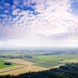 Ländlicher Landschaftshintergrund mit Betriebsfeldern und majestätischen Wolken Lizenzfreie Stockfotos