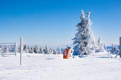 Ländlicher Winterhintergrund der Ferien mit weißer Kiefer, Zaun, Schneefeld, Berge Stockbild