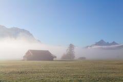 Ländliches Ackerland in den Alpen während des nebelhaften Sonnenaufgangs Lizenzfreies Stockbild