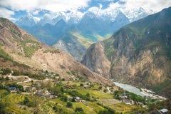 Ländliches chinesisches Dorf unter Schneebergen mit Fluss stockfotografie