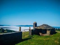 Ländliches Haus von Felsen und von Steinen mit einem Zaun und Ranch auf einem gree lizenzfreie stockfotografie